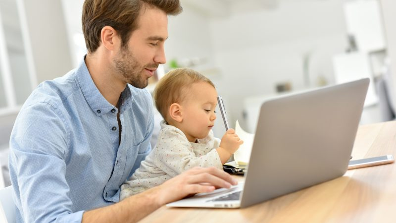 Busy businessman working from home and watching baby